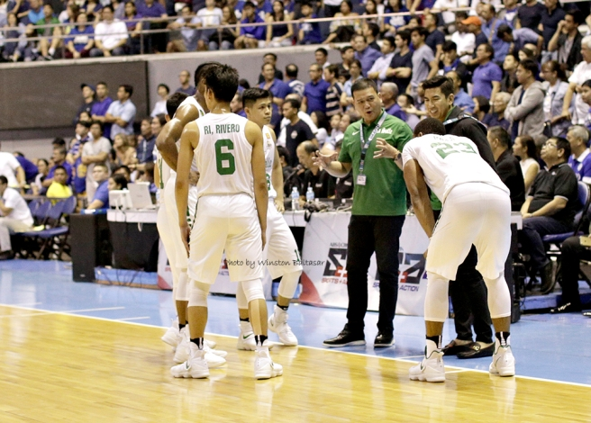 Coach Louie Gonzalez in a huddle with the Green Archers
